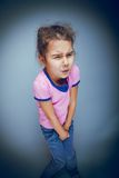 Girl child badly wants the toilet on a gray Stock Photo