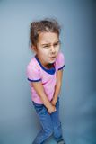 Girl child badly wants the toilet on a gray Stock Image