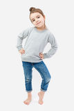 Girl child barefoot in jeans and a gray pullover Royalty Free Stock Image