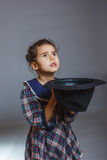 Girl child beggar holding hat on a gray background Stock Image