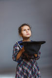 Girl child beggar holding hat just money on a gray Royalty Free Stock Images