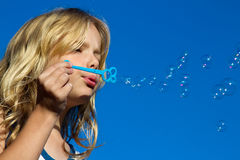 Girl child blowing bubbles. Beautiful blond girl blowing bubbles with a blue sky background Royalty Free Stock Photography
