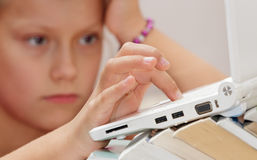 Girl child with a book looking laptop. Royalty Free Stock Photography