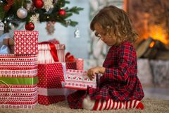 girl child celebrates Christmas at home by the fireplace and Christmas tree stock photography