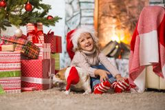 Girl child celebrating a happy Christmas at home by the fireplac stock photos