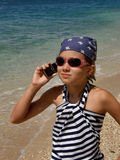 Girl (child) with cell on sand beach Stock Photography