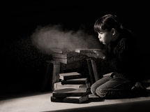 Girl child discovering hidden books in attic Stock Images