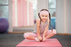 Girl child doing fitness exercises in health club, stretching in exercise. Workout, wearing sportswear, indoor full length, pink color. Keeping our bodies fit stock images