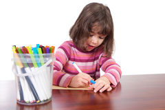 Girl child drawing art with kids colored markers. Young girl drawing on table with colored markers. Isolated on white Royalty Free Stock Image