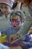 Girl child with drawings on the face of the festival. Cats in St. Petersburg, Russia royalty free stock photo