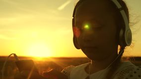 Girl child dreams to music in the sun. teen girl listening to music and watching the sunset. Happy girl dancing in. Headphones in the rays of a beautiful stock footage