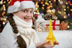 Girl child dressed in santa hat with eiffel tower toy and christmas gifts on dark illuminated background, happy new year and winte Stock Photo