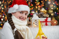 Girl child dressed in santa hat with eiffel tower toy and christmas gifts on dark illuminated background, happy new year and winte Royalty Free Stock Photo