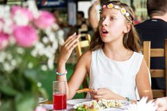 Girl child eating pizza in cafe Stock Images