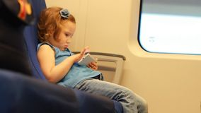 Girl child entertaining with smartphone in train. Baby playing game on the mobile phone in the express train.  stock footage