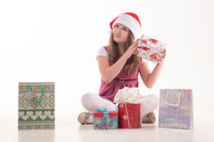 Girl child with a gift in a Santa hat. Girl teenager with a gift in a Santa hat Stock Photos