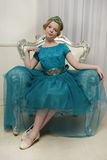 The girl child in the glamorous dress. Aqua on the couch Royalty Free Stock Photos