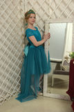 The girl child in the glamorous dress standing next to the mirror, admiring herself Stock Image