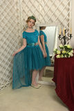 The girl child in the glamorous dress standing next to the mirror, admiring herself Royalty Free Stock Photos