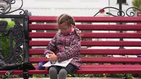 Girl child with glasses draws a picture in his album. A girl sits on a park bench.