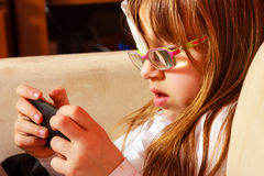Girl child in glasses playing games on smartphone at home Royalty Free Stock Image