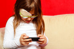 Girl child in glasses playing games on smartphone at home Stock Photos