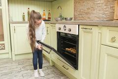 Girl child in gloves waiting for baking muffins or cupcakes near oven Royalty Free Stock Photo