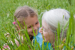 Girl child and Grandmother having fun outside. Girl laughing and having fun with her grandmother as they lie in long green grass Stock Image