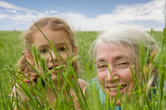 Girl child and grandmother together outside. Young girl and grandmother hiding and watching in long grass Stock Photography