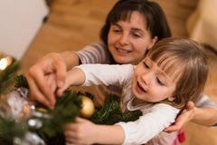 Girl child hanging bauble with help of her mother Stock Photo