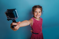 Girl child holding a camera in his hand shooter royalty free stock images