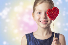Girl child holding a heart shaped lollipop . The effect of tonin Royalty Free Stock Image