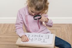Girl child holding piece of paper with word TECH EXPERT. royalty free stock photography