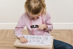 Girl child holding piece of paper with a word TECH EXPERT. royalty free stock photos