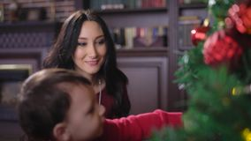 A girl with a child at home at the Christmas tree. Brunette looking at the child and smiling. The kid plays with a stock video