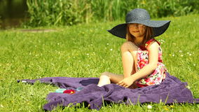 Girl child kid in straw hat relaxing on the meadow Royalty Free Stock Photography