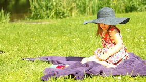 Girl child kid in straw hat relaxing on the meadow Stock Image