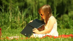 Girl child kid in sunglasses using tablet on the meadow stock footage