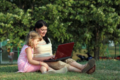 Girl and child with laptop in park Royalty Free Stock Photo