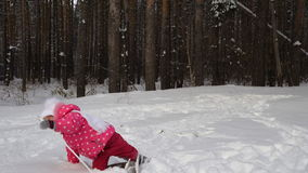Girl child is learning to ski. But she do not always get and she falls on the snow. Beautiful day in the winter forest stock video