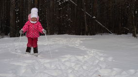 Girl child is learning to ski. She slowly slides on skis in soft fresh snow. Beautiful day in the winter forest.  stock footage