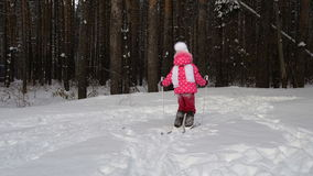 Girl child is learning to ski. She slowly slides on skis in soft fresh snow. Beautiful day in the winter forest stock video footage