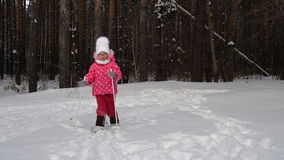 Girl child is learning to ski. She slowly slides on skis in soft fresh snow. Beautiful day in the winter forest stock video