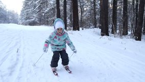Girl child is learning to ski. She slowly slides on skis in soft fresh snow. Beautiful day in the winter forest. Walk in. The snowy forest. FullHD stock video footage