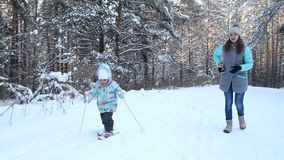 Girl child is learning to ski. She slowly slides on skis in soft fresh snow. Beautiful day in the winter forest. Woman. Teaches a child to ski. FullHD stock video footage