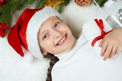 Girl child lie in christmas decoration on white fur, face closeup, dressed in santa hat, winter holiday concept, xmas tree Royalty Free Stock Images