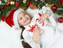 Girl child lie in christmas decoration on white fur, face closeup, dressed in santa hat, winter holiday concept, xmas tree Stock Image