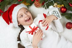 Girl child lie in christmas decoration on white fur, face closeup, dressed in santa hat, winter holiday concept, xmas tree Stock Images