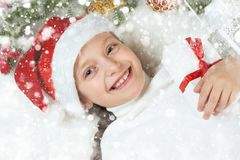 Girl child lie in christmas decoration on white fur, face closeup, dressed in santa hat, winter holiday concept, xmas tree Stock Photography