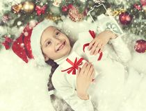 Girl child lie in christmas decoration on white fur, yellow toned, face closeup, dressed in santa hat, winter holiday concept, xma Royalty Free Stock Images
